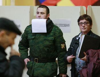 Военнослужащий срочной службы внутренних войск МВД РФ с бюллетенем для голосования на одном из избирательных участков города Москвы. Фото РИА Новости