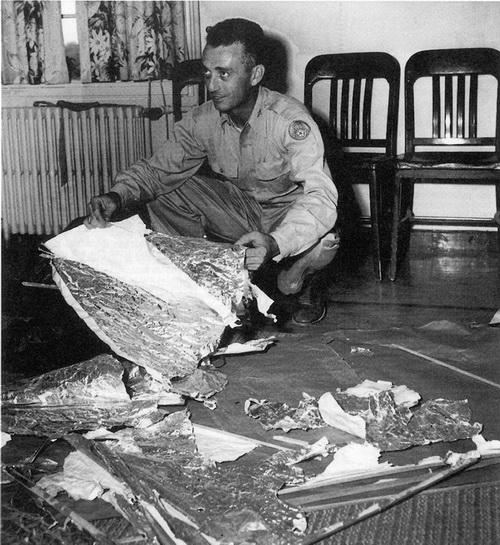 Майор Джесси Марсель с военного аэродрома г. Розуэлла с обломками, обнаруженными в 75 милях на северо-запад от г. Розуэлла, штат Нью-Мексико, в июне 1947 г. Обломки были идентифицированы как цель радара. Фото: United States Air Force/AFP/Getty Images