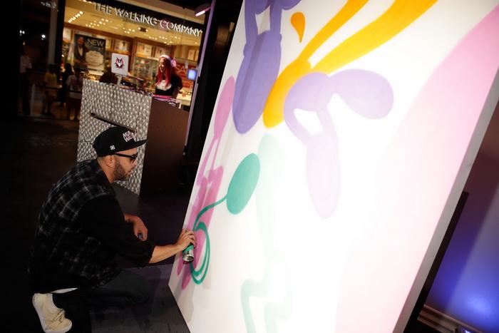 Художник Persue рисует на подиуме торгового центра «Показ мод» (Fashion Show) 20 августа 2013 года в Лас-Вегасе, штат Невада. Фото: Isaac Brekken/Getty Images for Pastry Fashion Show