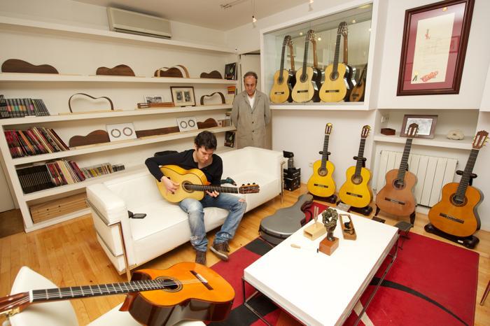 Профессиональный гитарист Яго Сантос выбирает гитару ручной работы, сделанную Фелипе Конде и его семьёй в мастерской Мадрида, Испания. Апрель 2013 года. Фото: Carlos Alvarez/Getty Images