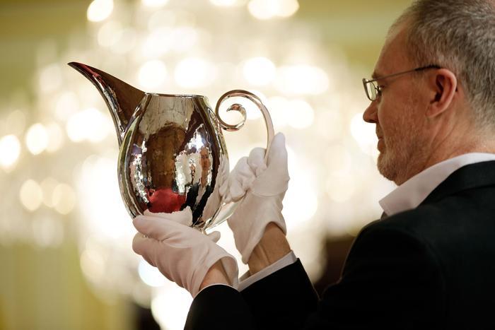 Серебряных дел мастер Грэхам Стеварт (Graham Stewart) держит кувшин, сделанный из серебра, на выставке украшений и других изделий из драгоценных металлов Goldsmiths' Fair 23 сентября 2013 года в Лондоне. Фото: Matthew Lloyd/Getty Images