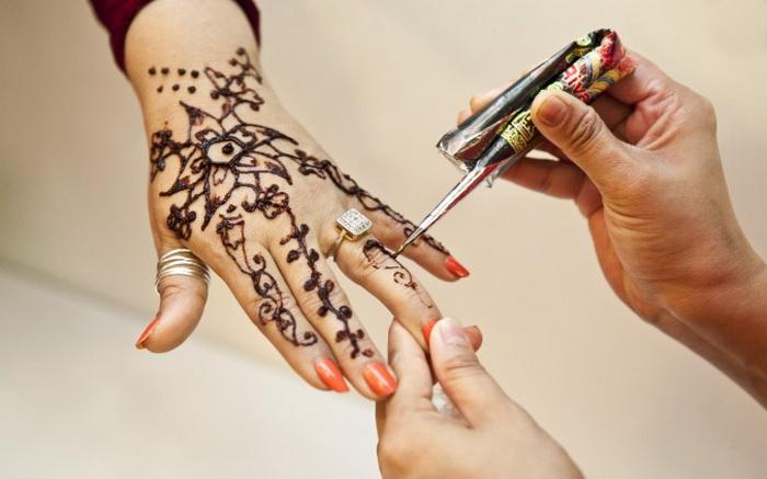 Женщине делают татуировку из хны. Фото: Samira Bouaou/The Epoch Times