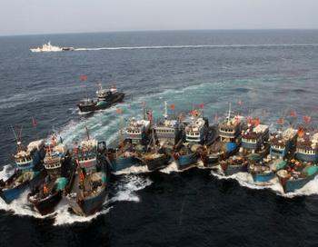 Снимок  16 ноября 2011 года показывает нелегальные китайские рыболовные суда, преследуемые вертолётом береговой охраны и коммандос на резиновых лодках в южнокорейских водах. Фото: Dong-a Ilbo/AFP/Getty Images