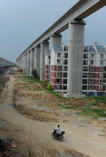 Жилые здания, находящиеся между бетонными опорами скоростной железнодорожной линии в Шуаньдунь  провинции Аньхой в Восточном Китае. Фото: STR/AFP/Getty Images)