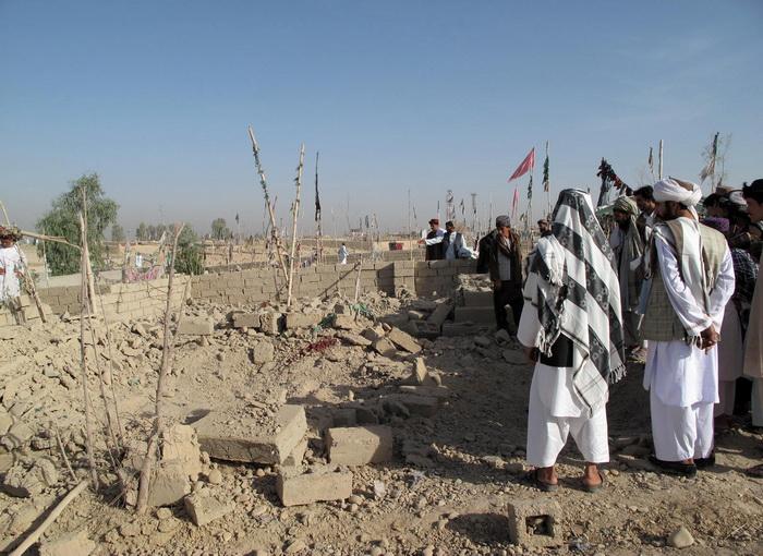 Афганские жители на месте взрыва бомбы в городе Лашкар Гах, столице провинции Гильменд, 19 августа 2012 года. Фото: STR/AFP/GettyImages