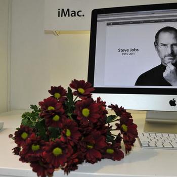 Цветы и яблоки перед портретом основателя компании Apple Стива Джобса у магазина re:Store. Фото РИА Новости