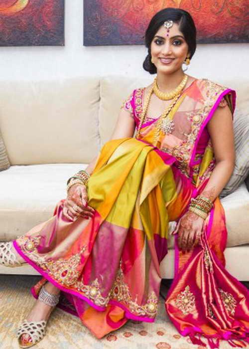 2. Индийская невеста сидит наряженная в шёлковое сари с орнаментом и золотые украшения. Фото: Lakiru
