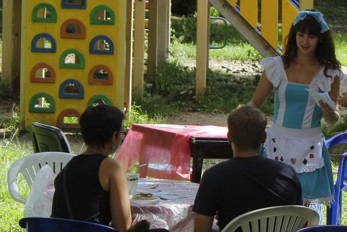 Официантка в костюме Алисы предлагает гостям отведать домашний лимонад. Фото: Николай Карпов/Великая Эпоха (The Epoch Times)
