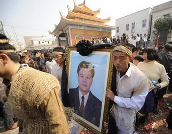 Родственники несут фотографию Сюэ Цзиньбо, который скончался в полицейском участке, Укань, Гуандун, 16 декабря 2011 года. Фото с сайта theepochtimes.com