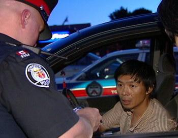 Полицейский Торонто задаёт вопросы Лу Пину, который доставлял таблоид с клеветой на Фалуньгун в июне 2007 года (Интернет-фото). Фото с сайта theepochtimes.com
