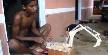 Уэсли играет с самодельным экскаватором. Фото сделано из YouTobe.