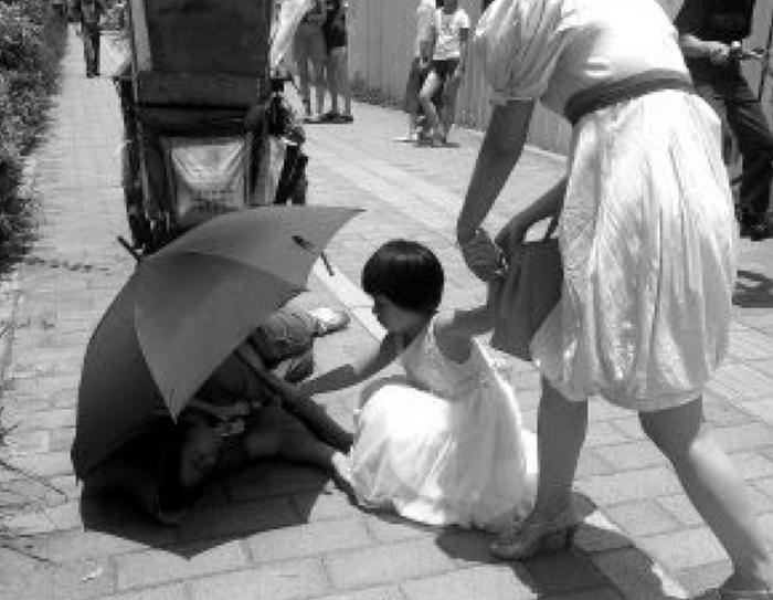 Постановочное фото: девочка держит зонт над потерявшей сознание женщиной. Фото: Screenshot/Secret China