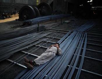 Работник металлургического комбината спит на стальных прутьях, Исламабад, Пакистан, 29 ноября 2010 года. Фото: Карл Де Соуза/AFP/Getty Images.