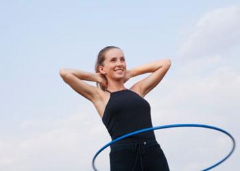 Упражнения с гимнастическим обручем помогут скинуть лишний жир на животе. Фото: Vstock LLC/Vladimir Godnik/Getty Images