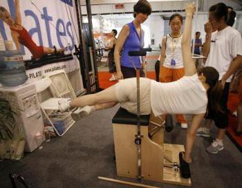 17 июля 2006 года женщина тестирует тренажер для выполнения упражнений пилатес на фитнесс-выставке в Пекине. Фото: Frederic J. Brown/AFP/Getty Images