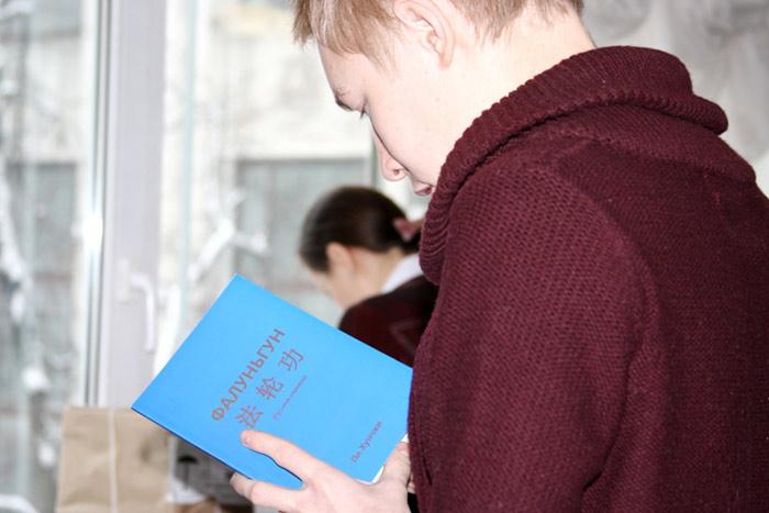 Молодой человек выбирает книгу «Фалуньгун» для чтения. Фото: Ульяна Ким/Великая Эпоха (The Epoch Times)
