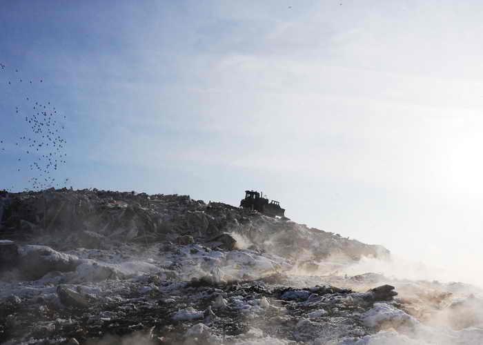 Крупнейший полигон твёрдых бытовых отходов на Волхонском шоссе, принимавший половину мусора Санкт-Петербурга, был отнят у собственника, заблокирован прокуратурой и подожжён неизвестными с нескольких сторон – так что тлеть, испуская удушливый дым, он теперь может годами. Фото: OLGA MALTSEVA/AFP/Getty Images