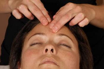 Женщине делают массаж, массажистка работает над чакрой, которая имеет, как считают восточные духовные учения, большую духовную силу и также связана с шишковидным телом в мозгу. Фото: Shutterstock*