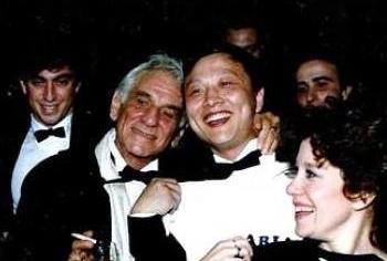 Брайт Шэн с Ленардом Бернстайном (С) и исполнителями в 1988г. после премьеры «Арий и Баркарол», музыки, сочиненной Леонардом Бернстайном и оркестрованной Брайтом Шэном. (Фото предоставлено мистером Шеном)