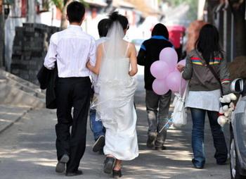 Перед свадьбой  пара проходит через старые переулки Хутун в Пекине. Фото: Frederic J. Brown/AFP/Getty Images