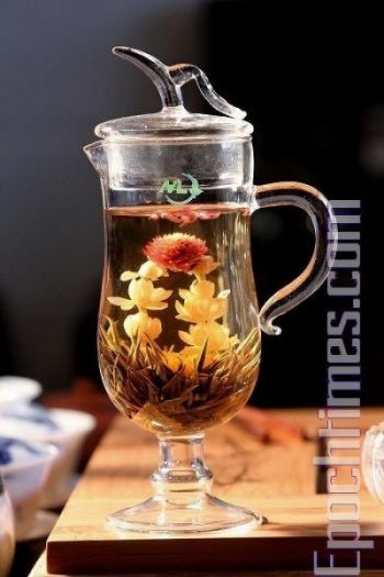 Дэнни приготовил цветочный чай. Засушенные цветы и зеленые почки чая расцвели в кружке горячей воды. Фото: Чень Мин/Великая Эпоха