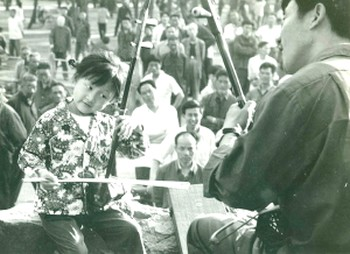 Когда Ци Сяочунь было шесть лет, отец научил ee играть на эрху, они играли с ним ежедневно. Во время репетиций они часто были окружены толпой людей, которая часами слушала музыку, отбивая такт руками и ногами. Фото Epoch Times