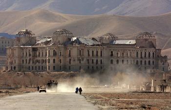 Афганские люди идут по улице в Кабуле, с разрушенным дворцом прежнего Афганского Премьер-министра Хэфизалло Амина. Фото:  ALEXANDER NEMENOV/AFP/Getty Images