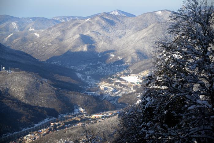 Общий вид села Эсто-Садок(Л) и «Красной поляны» (Ц) недалеко от курорта «Роза Хутор»  в Сочи, 3 февраля 2013 года. Фото: KIRILL KUDRYAVTSEV/AFP/Getty Images