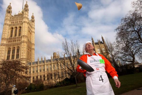 Английские парламентарии подбрасывают блины во время ежегодной Блинной гонки, вторник масленицы, 9   февраля 2010 г., Лондон. Фото: Oli Scarff/Getty Images