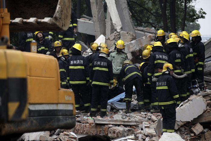 Спасатели пытаются высвободить людей из руин жилого дома после взрыва газа на территории газового предприятия в китайском городе Сучжоу 11 июня 2013 г. Фото: ChinaFotoPress/Getty Images