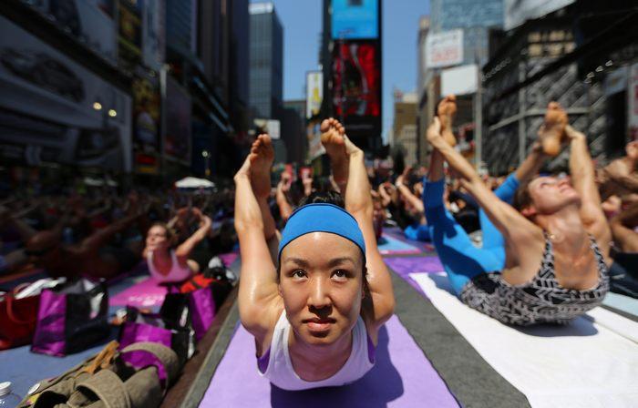 Тысячи людей отметили день летнего солнцестояния упражнениями йоги на Таймс-сквер в Нью-Йорке 21 июня 2013 г. Фото: Mario Tama/Getty Images