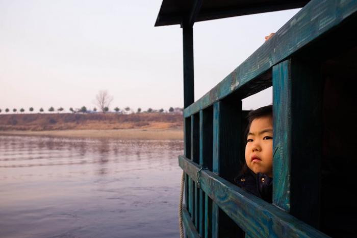 Маленькая девочка на туристическом судне на реке Имджин. Фото: Джерод ХОЛЛ