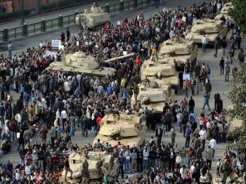 Колонна танков Abrams выстраивается в ряд вдоль улицы, в то время как египетские демонстранты собираются на площади Тахрир в Каире 30 января 2011 года, на шестой день акций протеста против режима Хосни Мубарака. (Мигель Медина / AFP / Getty Images)