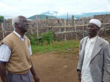 Абель Томас Бабу Симваба (слева) стоит со своим другом Пегу (справа), который заботился о корове Бабу в течение шести месяцев в его отсутствие. Бабу говорит, что хочет оплатить доброту своего друга, отдав ему теленка от коровы. (Ондреж Хореки / The Epoch Times)