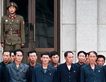 На фото, сделанном Chosun Daily News 29 сентября, северокорейские граждане стоят рядом с солдатом, охраняющим приграничную деревню Панмунчжон, расположенную между Северной и Южной Кореей. Фото: LEE TAE-KEBNG/Getty Images
