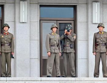 Северокорейский солдат фотографирует южную часть приграничной деревни Панмунчжон 27 июля - в день 57-й годовщины подписания перемирия в Корейской войне. Фото: KIM JAE-HWAN/AFP/Getty Images