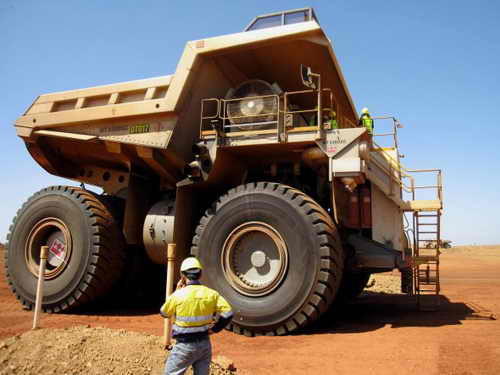 Рабочий стоит радом с огромным грузовиком на железорудной шахте, принадлежащей китайской компании Citic Pacific Mining, регион Пилбара, Западная Австралия, 5 марта 2010 года. Фото: Amy Coopes/AFP/Getty Images