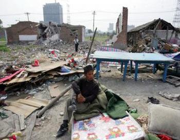 Житель Пекина сидит на матрасе  на месте разрушенного дома в районе Таянгун, 10 мая 2007 г. В ночь на 9 мая неизвестными было снесено около 26 домов.  Жилищная реформа в Китае приводит к лишению людей своего жилья. Фото: China Photos/Getty Images