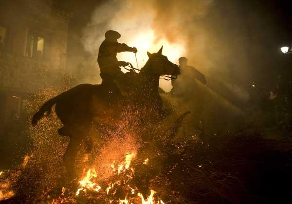 Традиции. В центральной части Испании всадники перепрыгивают через костер в день святого заступника животных. Фото: JAVIER SORIANO /AFP/Getty Images