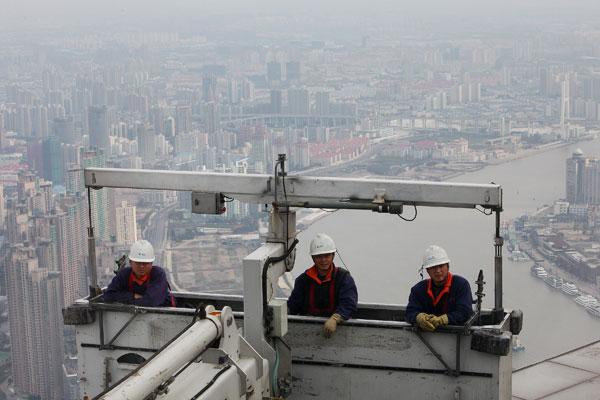 Expo 2010.  Мойщики окон в подвесных люльках на высоте 492 м на здании Финансового центра в Шанхае. Фото: Feng Li/Getty Images