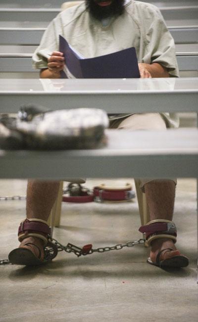 Гуантанамо (Куба). Арестованный читает журнал в лагерной библиотеке. Фото:  PAUL J. RICHARDS/AFP /Getty Images