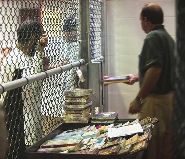 Гуантанамо (Куба). Выдача литературы в лагерной библиотеке. Фото:  PAUL J. RICHARDS/AFP /Getty Images