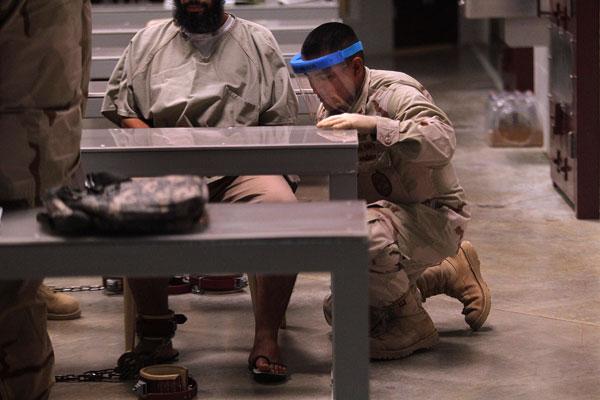 Гуантанамо (Куба). Заключенного освобождают от кандалов. Фото:  John Moore/Getty Images