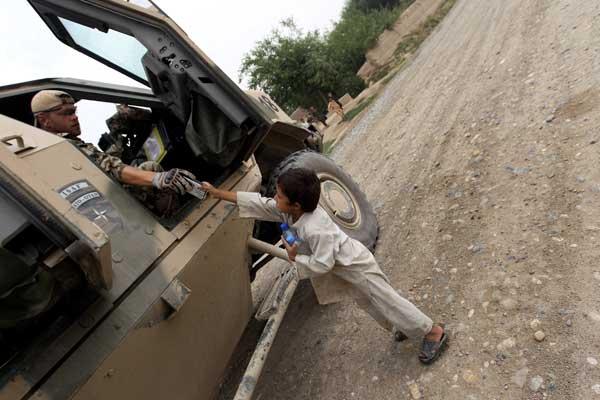Пехотинец дает пакетик печенья и бутылку воды афганскому ребенку. Фото: Miguel Villagran/Getty Images