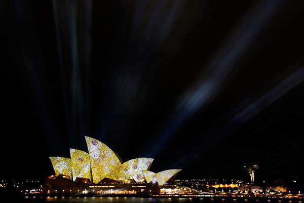 Здание сиднейского Оперного театра освещается лучами спроецированного света. Фото: Lisa Maree Williams/Getty Images