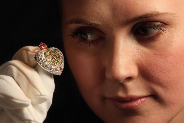 Служащая Сотбис держит алмазную брошь с изумрудами и рубинами, созданную Картье в 1957 г.  Фото: Dan Kitwood/Getty Images
