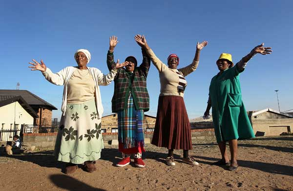 Женщины приветствуют карнавальную процессию 5 июня 2010 в пригороде Soweto Иоганнесбурга, Южная Африка. Фото: John Moore/Getty Images