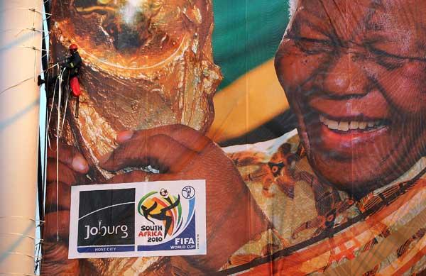 Рабочий закрепляет гигантский баннер с Нельсоном Мэнделе в центре г. Иоганнесбурга, Южная Африка.  Фото: John Moore/Getty Images