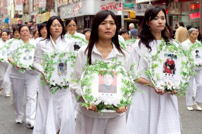 Последователи Фалунь Дафа несут фотографии погибших в преследовании в Китае. Фото: Samira Bouaou/The Epoch Times