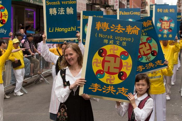 Последователи Фалунь Дафа разных стран несут макеты основной книги учения «Чжуань Фалунь», которая переведена на 38 языков мира. Фото: Matthias Kehrein/The Epoch Times